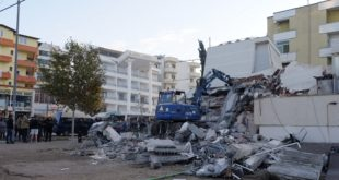 People stand near a damaged building after an earthquake in Durres, western Albania, Tuesday, Nov. 26, 2019. A strong earthquake has shaken Albania, killing at least four people, injuring 150 and collapsing buildings. (AP Photo/Hektor Pustina)